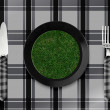 Green grass on black plate — Stock Photo