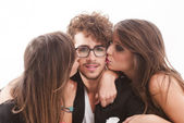 Two young attractive women kissing man — Stock Photo