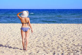 Woman on the beach with white hat — Stock Photo