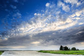 Dark clouds above a lake — Stock Photo