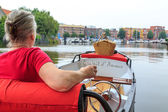 Woman in boat with picnic basket — Stock Photo