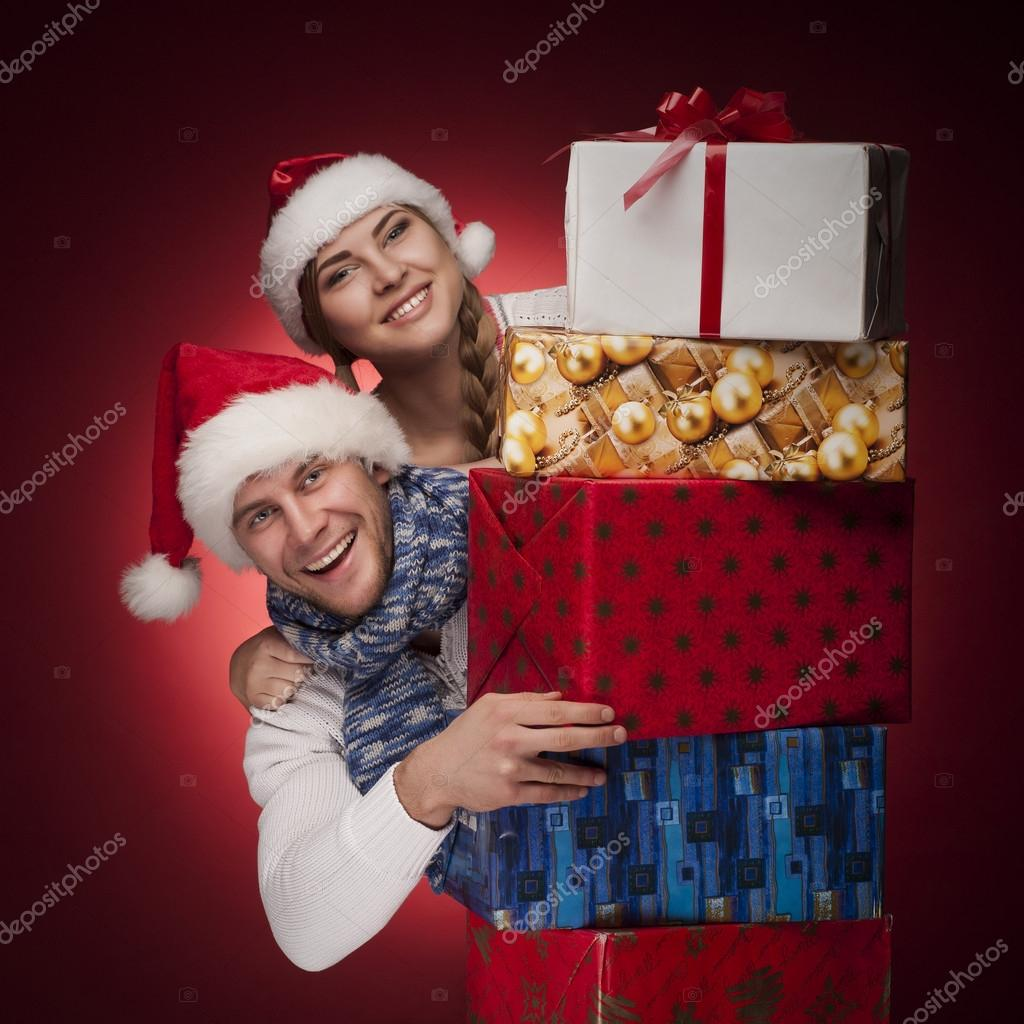 Studio shoot of young couple in Santa hats with presents isolated — Stock Photo #14835041