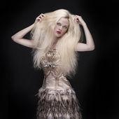 Vacker kvinna med långt hår på mörk bakgrund — Stockfoto