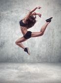 Young woman dancer with grunge wall background — Stock Photo