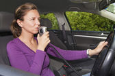 Woman blowing into breathalyzer — Stock Photo