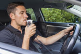 Man blowing into breathalyzer — Stock Photo