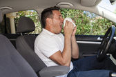 Man sneezing in car — Stock Photo