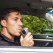 Man blowing into breathalyzer - ストック写真