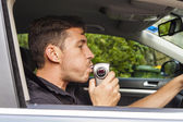 Man blowing into breathalyzer — Stockfoto