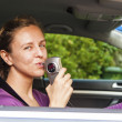 Woman blowing into breathalyzer - Stock Photo