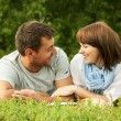 Smiling couple and lying on the grass outdoor — Stock Photo