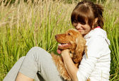 Happy young girl embracing her dog on the grass — Stock Photo
