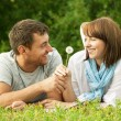 Stock Photo: Young mgiving flower to girlfriend
