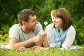 Young man giving a flower to girlfriend — Stock Photo
