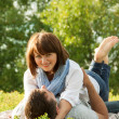 Young couple laying down in grass and hugging each other — Stock Photo