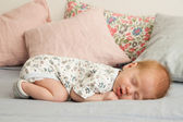 Cute newborn baby boy sleeping on a blanket — Stock Photo
