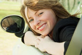 Smiling driver woman looking back while popping head out the window of new car — Stock Photo