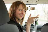 Happy smiling driver woman showing car key sitting in a new auto — Stock Photo