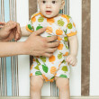 Baby is standing with help — Stock Photo #25478879