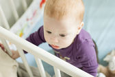 Baby boy trying to stand up in his cot — Stock Photo