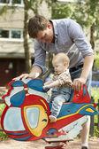 赤ちゃんの父親と息子の遊び場で楽しい時を過す — ストック写真