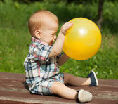 Happy baby playing with a ball outdoors — Stock Photo