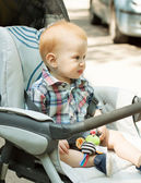 Adorable baby boy sitting in stroller — Stock Photo