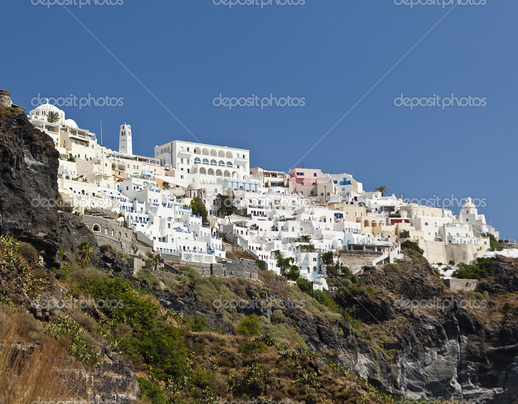 A view of the town of Thera on the Greek island of Santorini. The city of white buildings is built along the crater rim of an old volcano. — Stock Photo #14689583