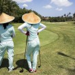 Stock Photo: Two Caddies On Bali Golf Course