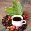 Fresh raw coffee beans, coffee cup with leaf — Stock Photo #12891662