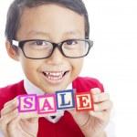 Schoolboy showing SALE word — Stock fotografie #12072282