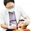 Asian dentist and his little patient — Stock Photo #12390772