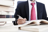 Businessman writes on a book — Stok fotoğraf