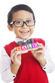 Smart asian boy with a sale sign — Stock Photo