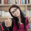 Successful student showing thumbs-up - Stock Photo