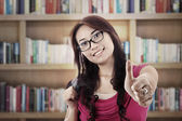 Student showing thumbs-up in library — Stock Photo