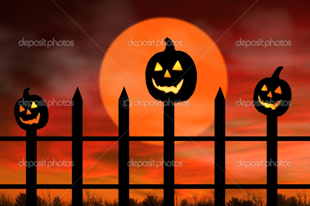 Halloween background with three black pumpkins in the fence glowing.  Stock Photo #12928100
