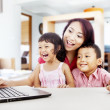 Happy family with laptop at home 1 — ストック写真