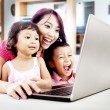 Happy family with laptop at home — Foto Stock