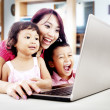 Stock Photo: Happy family with laptop at home