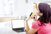 Thoughtful woman online shopping at home — Stok fotoğraf