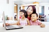幸福的家庭与便携式计算机在首页 1 — 图库照片