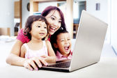 Happy family with laptop at home — Stok fotoğraf
