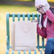 Shopping girl on the bench — Stock Photo