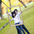 Young couple with wooden frame — Stock fotografie