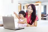 Familia alegre con ordenador portátil — Foto de Stock