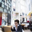 Business woman typing on laptop while having coffee — ストック写真