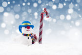 Snowman doll with candy cane — Stock fotografie