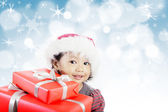 Little girl with red gifts — Stock Photo
