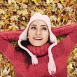 Happy woman laying on Autumn leaves — Stock Photo